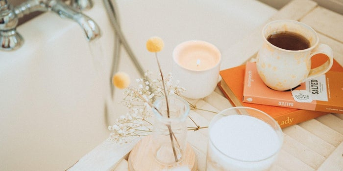 a bath with table with beauty products and drink