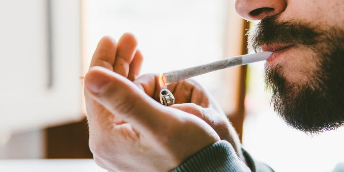 man lighting up his cannabis joint
