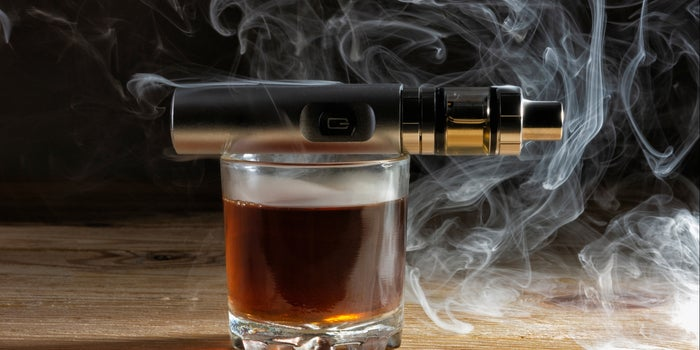cup of alcohol, with vape balancing on top