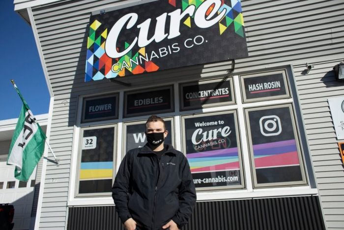 man stood in front of marijuana store named Cure