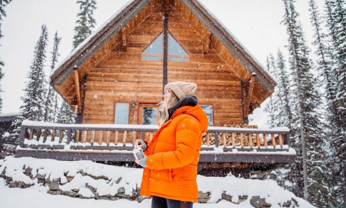 Woman outside cabin with snow