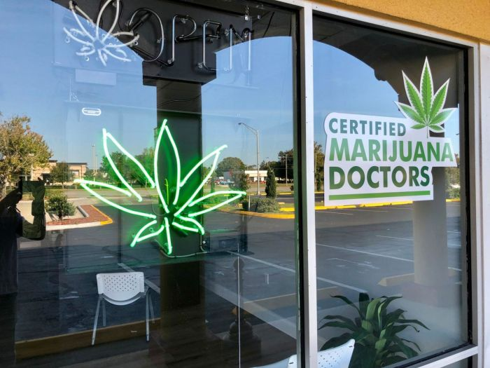 glass front of store painted with marijuana leaves