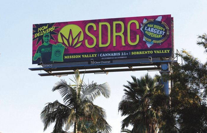 large signage advertising cannabis over some trees