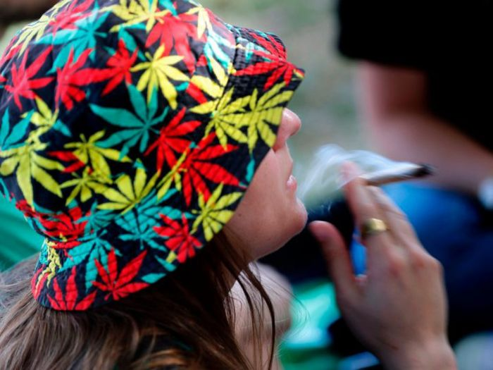 girl wearing colourful marijuana hat, smoking a joint.