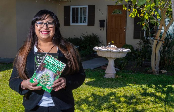woman holding stack of magazines in front of house