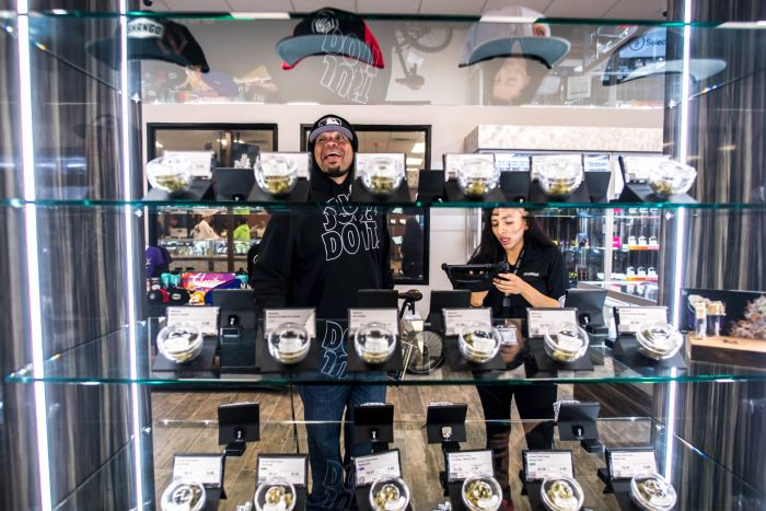 shelves filled with cannabis and customers in the background