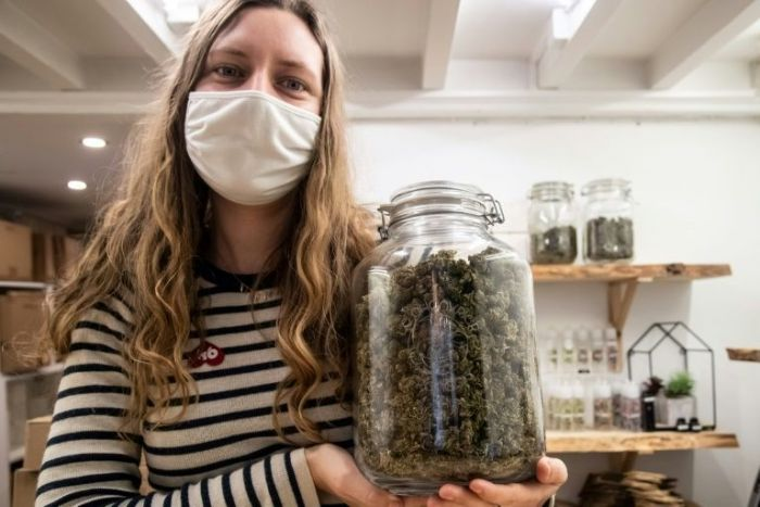 woman holding up glass jar filled with cannabis buds