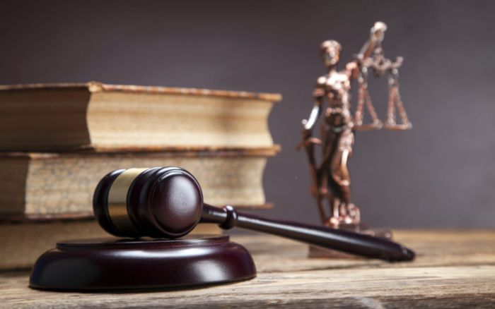 legal gavel, books, and a justice statue on a table
