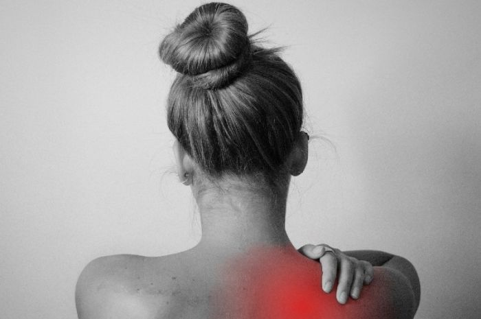 Woman with red spot on back indicating pain