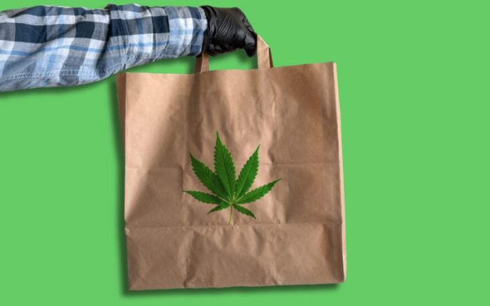 hand holding out brown paper bag with cannabis leaf with green background