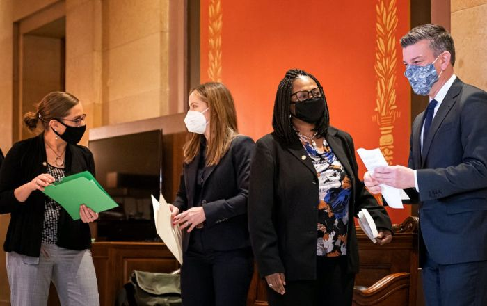 four politicians wearing masks