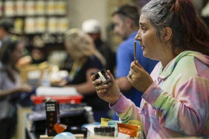 Woman smelling a cannabis joint at a store