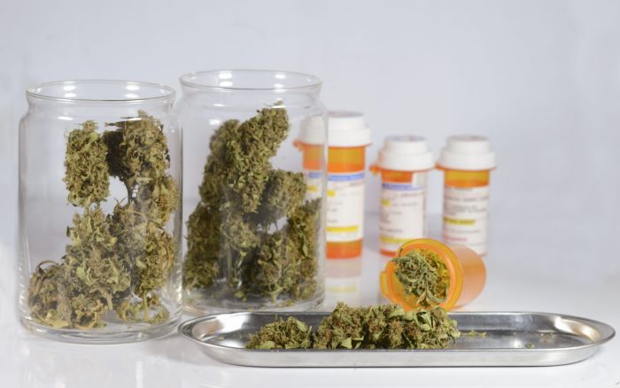 glass jars containing cannabis with medical bottles