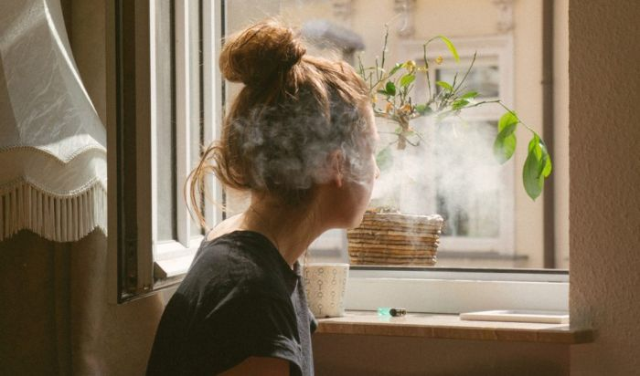 woman smoking out of a window