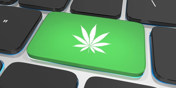 keyboard close-up with one key bright green with a white marijuana sticker on it
