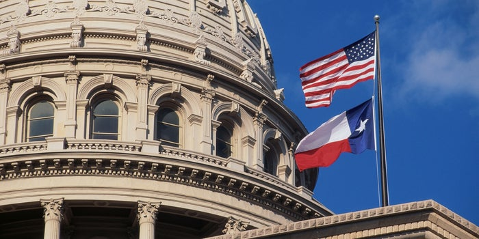 Texas state building with the us flag and texan flag flying