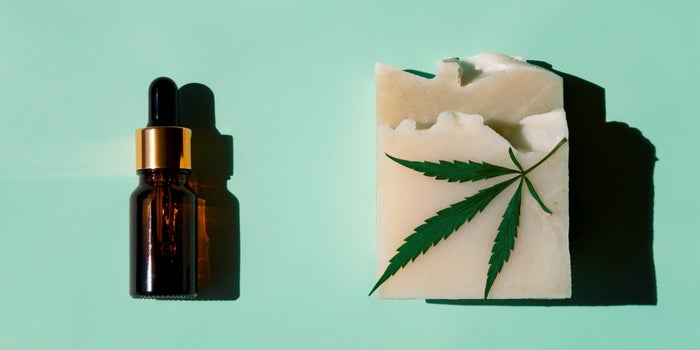 cannabis packaging with a cbd bottle against a green background