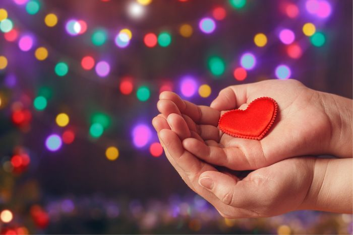 christmas lights and a hand holding a small plastic heart