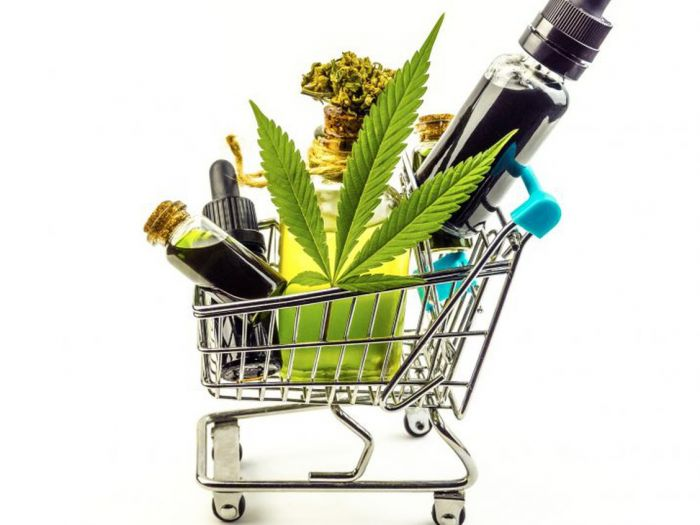 a small shopping cart filled with large cananbis leaf, vape, and marijuana with blank background