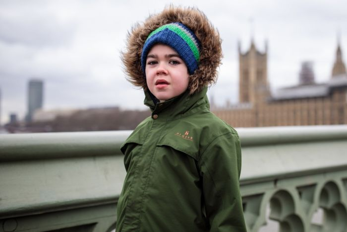 little girl on bridge in front of parliament buildings in London