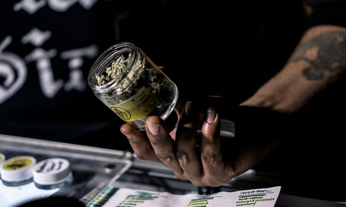 hand holding out glass jar containing cannabis