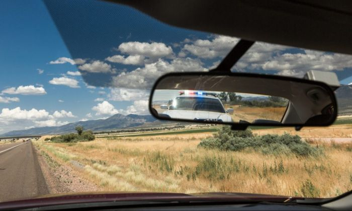 inside shot of car dashboard with view of a cop car in mirror