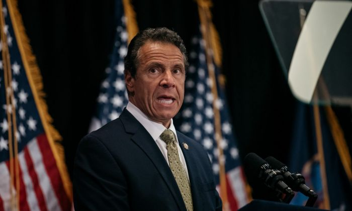 Andrew Cuomo in front of american flags