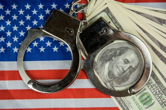 handcuffs on top of money and US flag