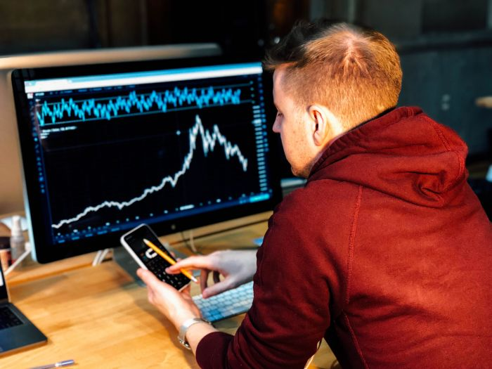 man sitting at computer playing the stock market