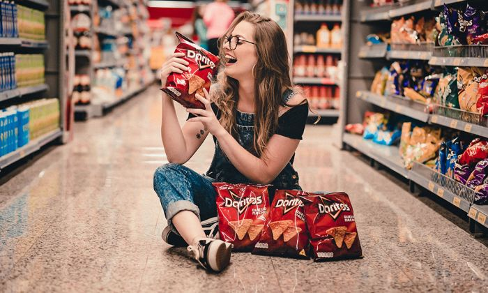 Woman in store isle with bag of chips