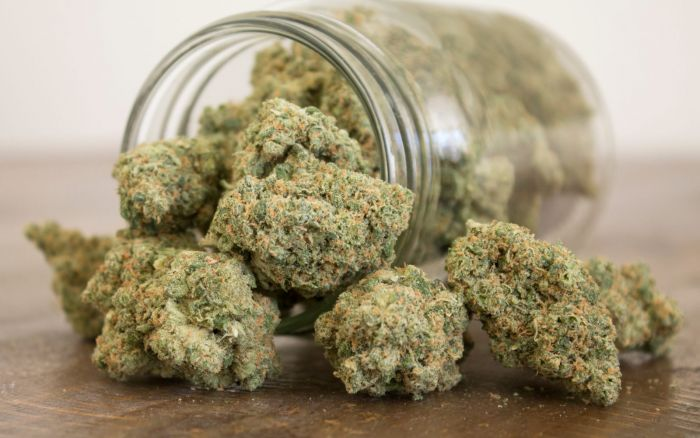 glass jar filled with cannabis tipped over on table