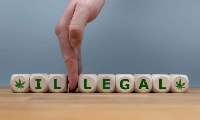 letter cubes spelling out Illegal with a finger separating the word legal